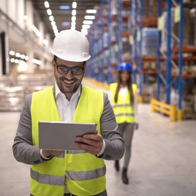 Warehouse manager reading report on tablet about successful delivery and distribution in warehouse logistics center.